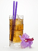 Rum drink with ice cubes and straws, orchid beside it