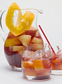 Fruity red wine punch in glass jug and glasses