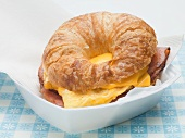 Croissant with scrambled egg, cheese & bacon on paper napkin