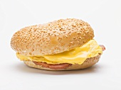 Sesame bagel filled with scrambled egg, cheese and ham