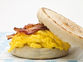 English muffin filled with bacon, scrambled egg & cheese (close-up)