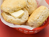 Scones in a plastic basket (one with butter)