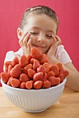Little girl, daydreaming, with a bowl of strawberries
