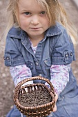 Little girl holding basket of pelleted manure