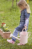 Little girl carrying water can through garden