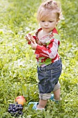 Little girl holding rice cake in grass