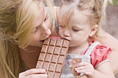 Mother and young daughter biting into a bar of chocolate