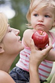 Mother offering young daughter a red apple