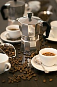 Espresso maker, cups of espresso and coffee beans