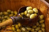 Eingelegte grüne Oliven in Holzfass und Kelle