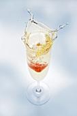 A glass of sparkling wine with strawberry (splash)