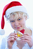 Girl in Father Christmas hat holding Father Christmas biscuit