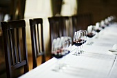 Table laid in white with glasses of red wine