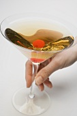 Hand holding a glass of Manhattan with cocktail cherry