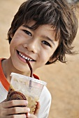 Smiling boy drinking iced cocoa