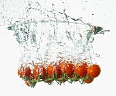 Cherry tomatoes falling into water