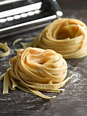 Home-made ribbon pasta in front of pasta maker