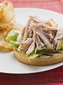 Strips of turkey on grilled bread roll, crisps