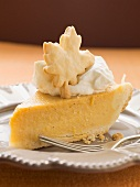 Piece of pumpkin pie with cream and pastry leaf