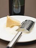 Parmesan, partly grated, with cheese grater on plate