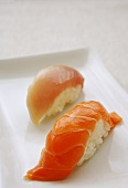 Two nigiri sushi made with salmon and tuna