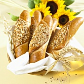 Several grain baguettes in a bread basket with sunflowers and ears of corn