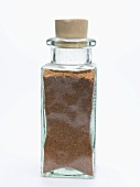 Grated nutmeg in small glass bottle
