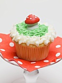 Muffin with fly agaric mushroom on cake stand