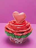 Cupcake with red marzipan rose and red pastry heart