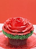 Cupcake with red marzipan rose against red background
