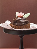 Chocolate cake with marzipan rose on cake stand