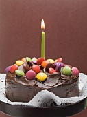 Chocolate cake with coloured chocolate beans and candle