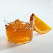 Orange jelly in glass, orange wedge beside it