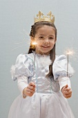 Little girl dressed as princess holding sparklers