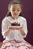 Little girl holding birthday cake