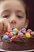 Little girl taking chocolate bean from birthday cake