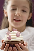 Little girl holding cupcake with sugar hearts