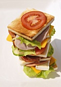 Tower of toast, ham, sausage, cheese, tomatoes and lettuce