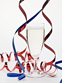 Glass of sparkling wine with party decorations