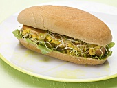 A hot dog with sprouts on a plate