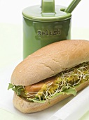 A hot dog with sprouts beside a relish pot