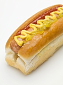 A hot dog with mustard, ketchup and gherkin