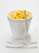 Macaroni and cheese in a polystyrene tub with spoon