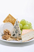 Cheese plate with crackers, nuts and grapes