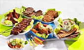 Various grilled dishes with salads