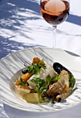 Fish and shellfish with vegetables, glass of rosé wine