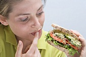 Young woman holding sandwich and licking her finger