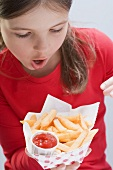 Girl holding chips with ketchup