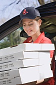 Woman in baseball cap delivering five boxes of fresh pizza