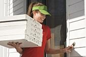Junge Frau vom Pizzaservice klingelt an der Tür